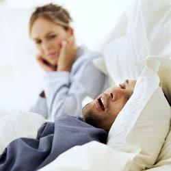 young woman trying to shut out the sound of her husband snoring