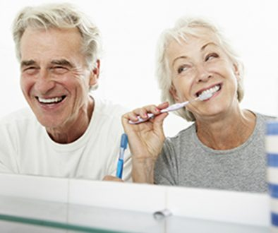 Couple in bathroom with woman brushing her teeth